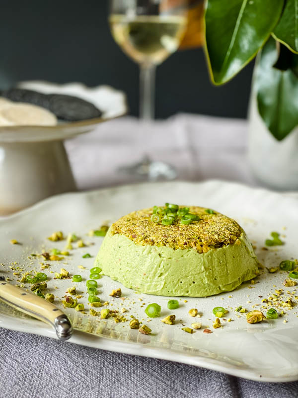 The Avocado Pistachio Pate is on a platter with crackers and a glass of wine in the background.