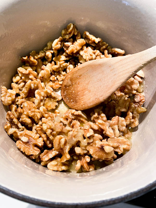 The raw walnuts have been added to a saucepan with the sugar mix.