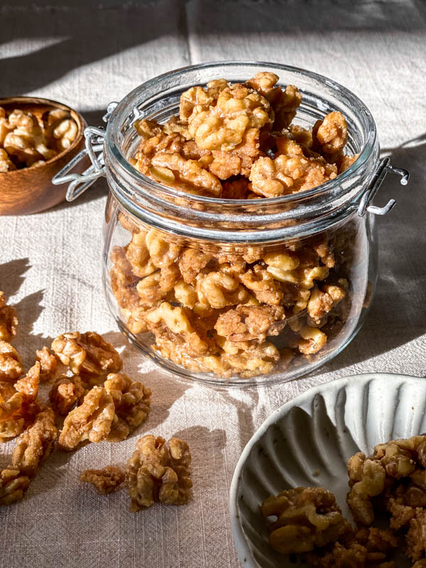 The jar of Candied Walnuts are sitting in the sunlight.