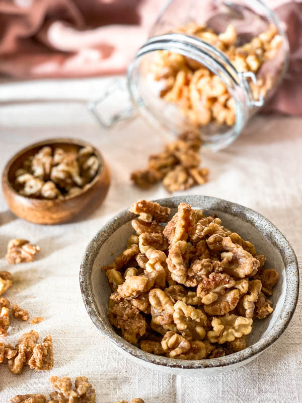 A bowl of Candied Walnuts with a jar in the background that is tipped over with some of the nuts spilling out onto the tablecloth.