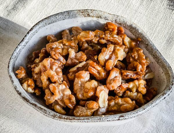 The Candied Walnuts in a bowl on a cream tablecloth.