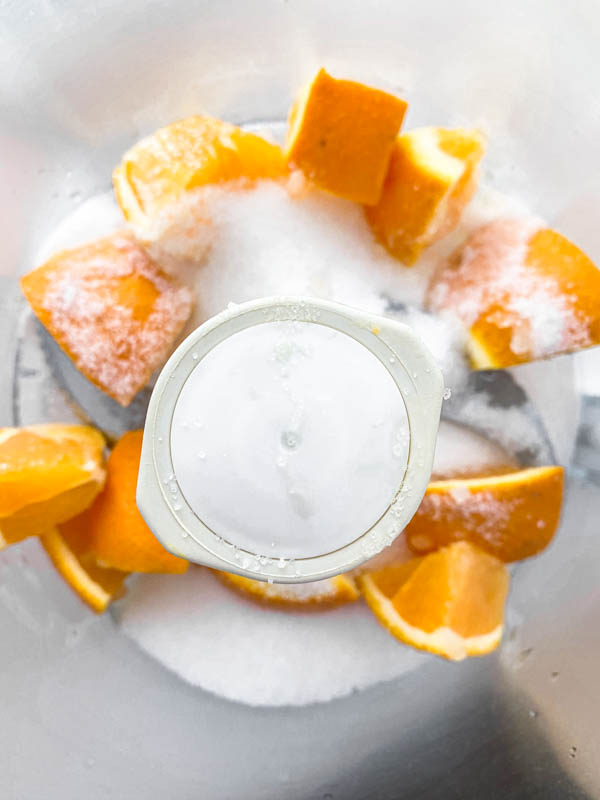 The chopped orange chunks are in the bowl of a food processor with the sugar ready to be blended.