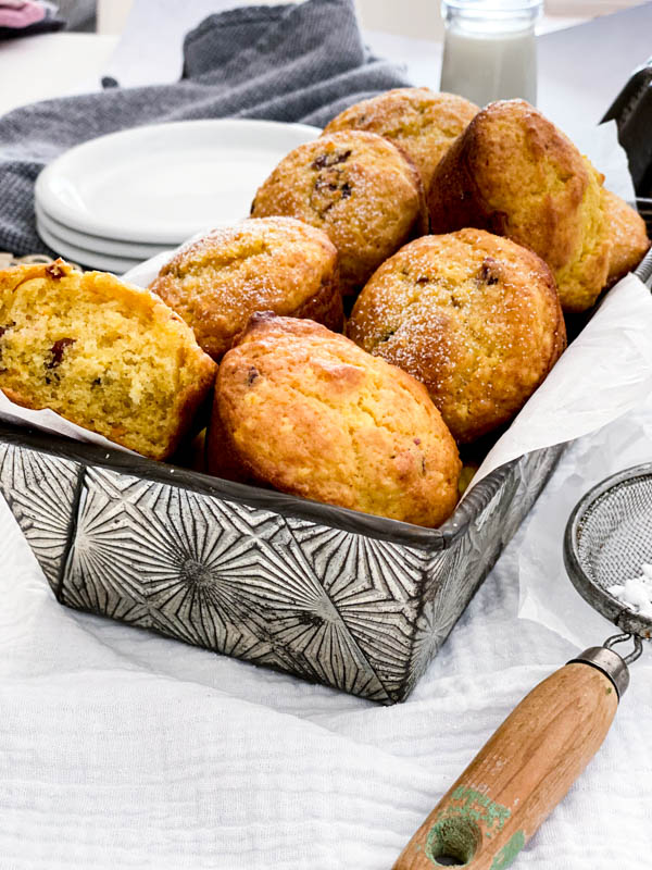 A loaf tin lined with baking paper is full of freshly baked muffins. There are plates and a glass of milk in the background and a small sieve with icing sugar in it, in the foreground.