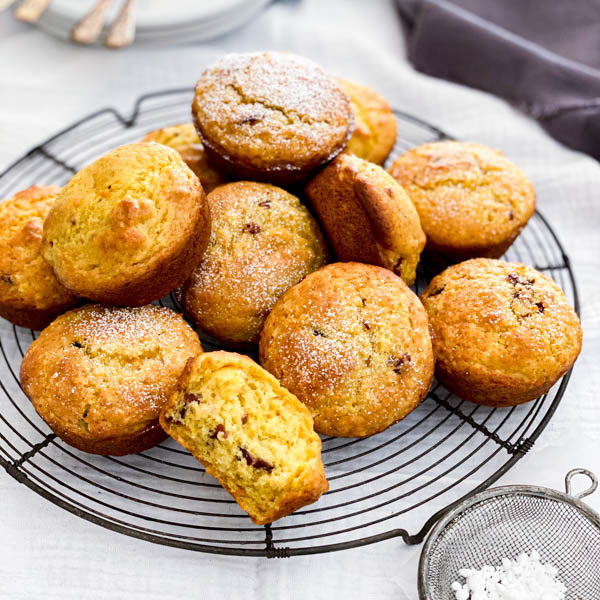 A pile of freshly baked Orange Cranberry Muffins are on top of a vintage cake resting rack.