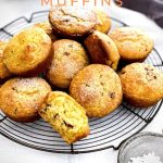 A pile of freshly baked muffins are on a round cake rack. Some are sprinkled with icing sugar.