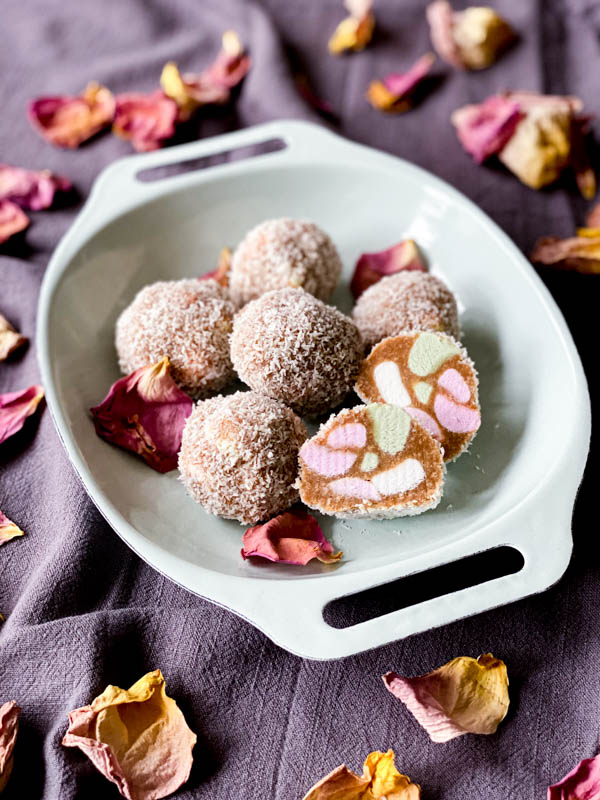 The Lolly Cake mixture is rolled into balls that have been rolled in coconut. The balls are on a plate with one of them sliced open to show the colourful inside. This shows another way to shape the Lolly Cake.