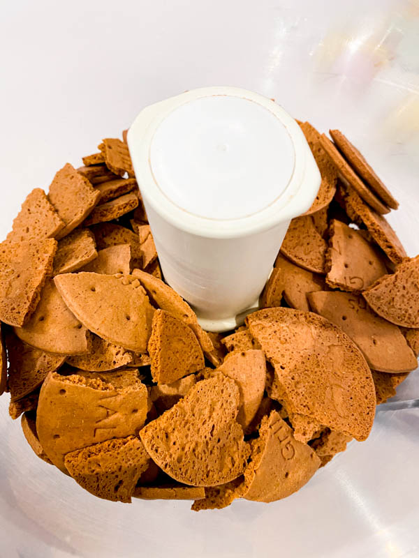 The broken malt biscuits are in the bowl of a food processor.