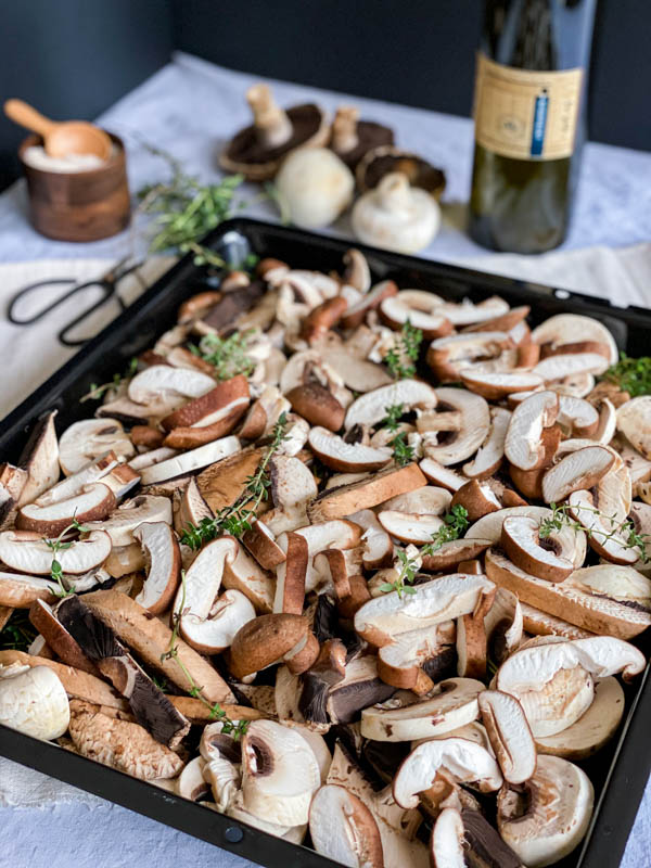 Raw sliced mushrooms are laid out on an oven tray with thyme sprigs sprinkled over. There is a bottle of olive oil in the background along with musrhrooms, herb scissors and a pinch pot of sea salt.