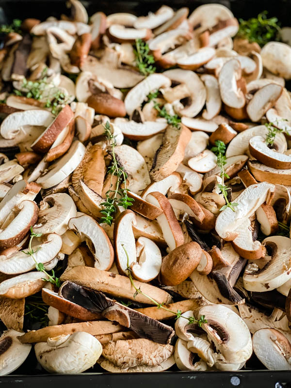 A close up of the raw sliced mushrooms with thyme sprigs scattered over the top.