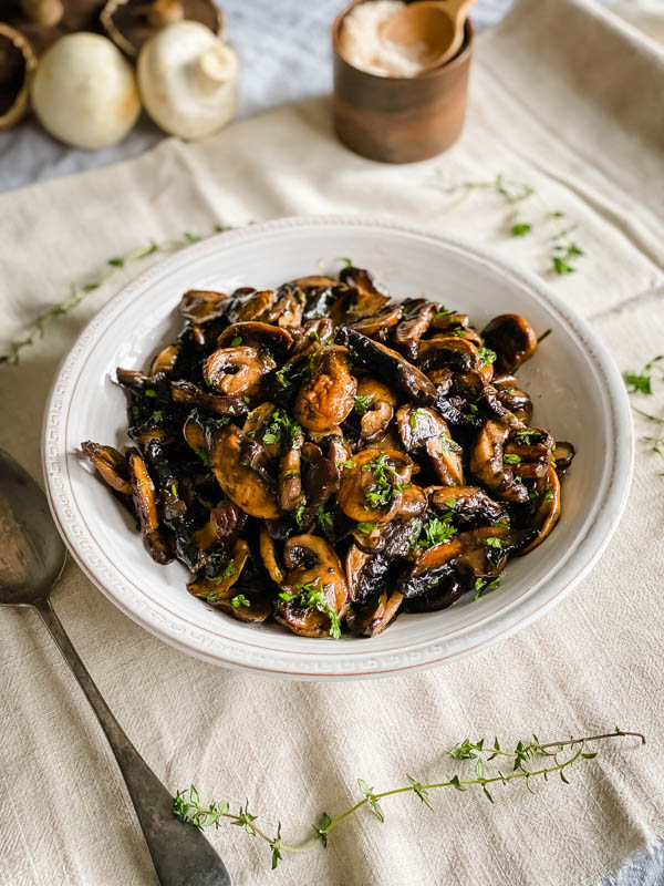 The roasted mushrooms are in a serving bowl sprinkled with parsley. Thyme sprigs are scattered around the bowl and there are whole mushrooms and a pinch bowl of sea salt in the background.