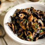 The Roasted Mushroom Medley is in a white bowl on a cream tablecloth.