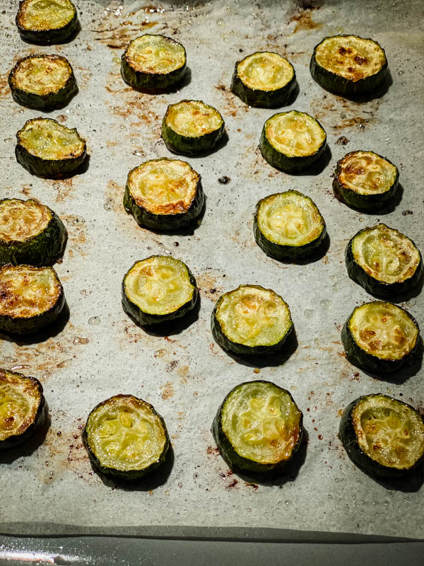 Slices of roasted zucchini on a baking tray.