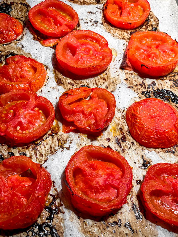 The roasted slices of tomato on an oven tray.