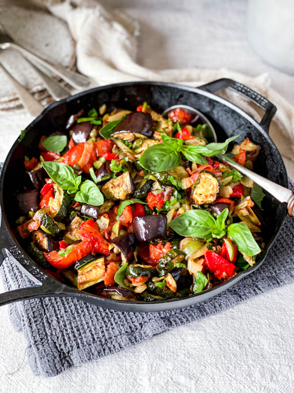 The Roasted Ratatouille Salad is in a black pan on a table with cutlery and plates in the background.