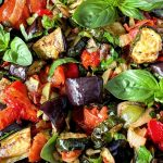 Close up of the Roasted Ratatouille Salad that is garnished with basil sprigs.
