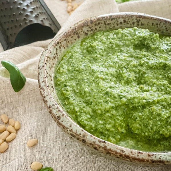 A close-up of the bowl of Basil Pesto with a mini cheese grater in the background.
