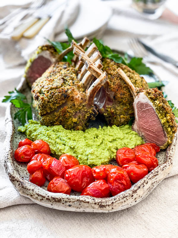 The platter of Herb Crusted Lamb Racks, pea puree and blistered tomatoes are on a table with cutlery and plates in the background.