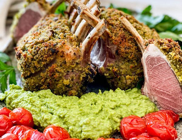 Close up of the cooked lamb racks with pea puree and blistered tomatoes. One of the racks has been cut into showing the beautiful pink lamb meat inside.