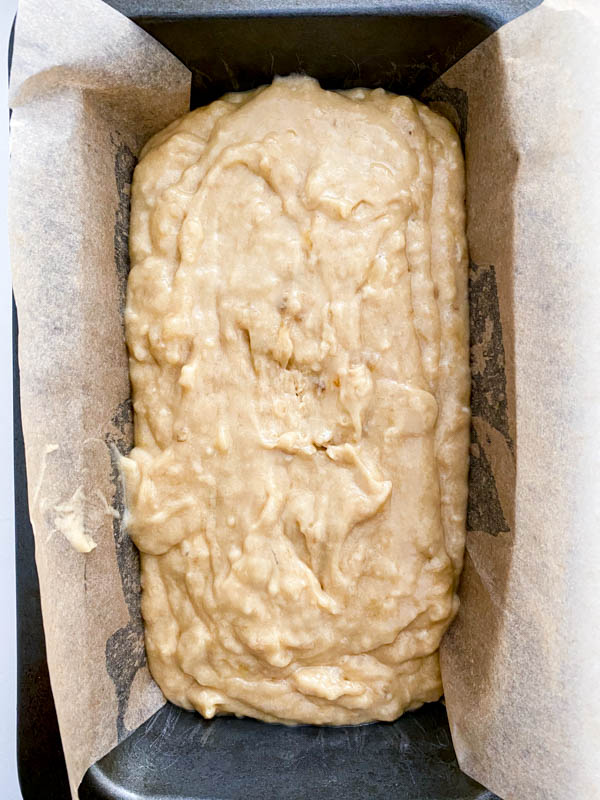 The batter is now in a loaf pan that is lined with baking paper.