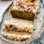 The Banana Cake is on a serving plate and has been frosted with Cream Cheese icing and decorated with walnuts and dried flowers.
