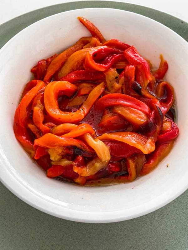 Roasted red capsicum slices in a bowl with olive oil drizzled over.