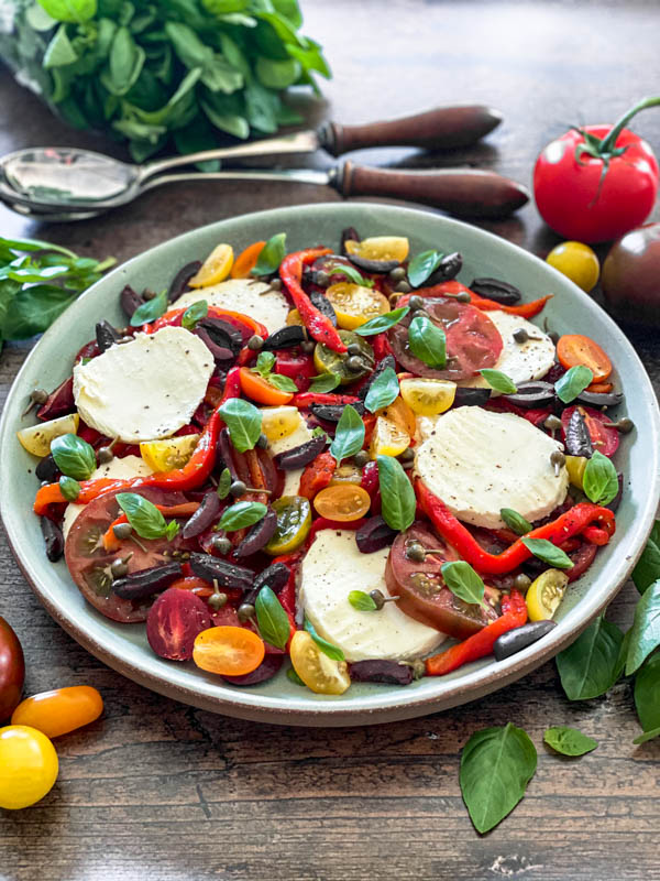 A platter of Caprese Salad with basil leaves and tomatoes surrounding it.