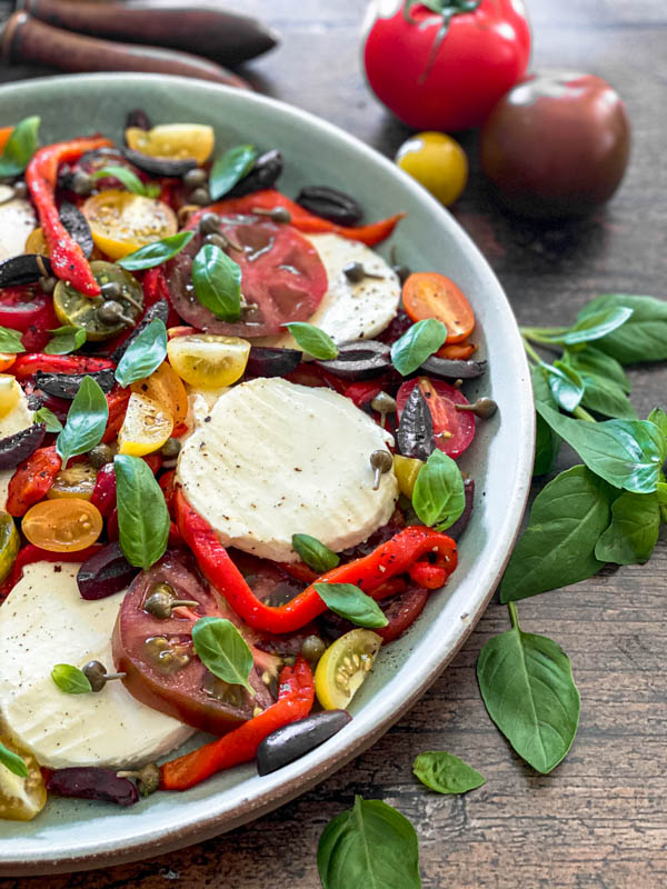This shows half the platter of Caprese Salad with basil leaves around it.