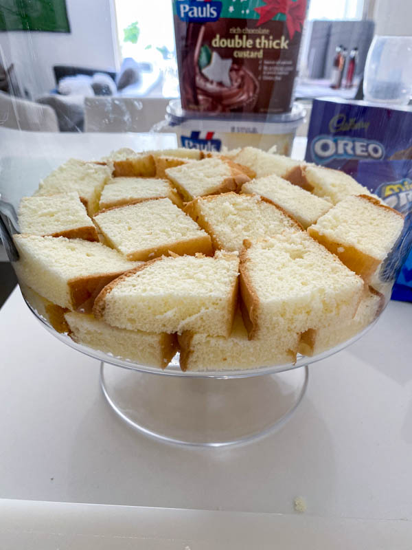 A layer of cubed sponge is placed in the bottom of a trifle bowl.