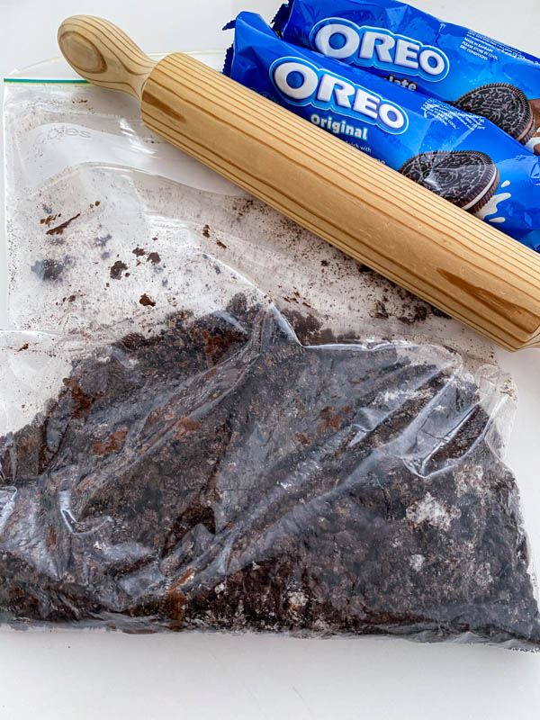 The Oreo biscuits have been crushed in a plastic bag using a rolling pin.