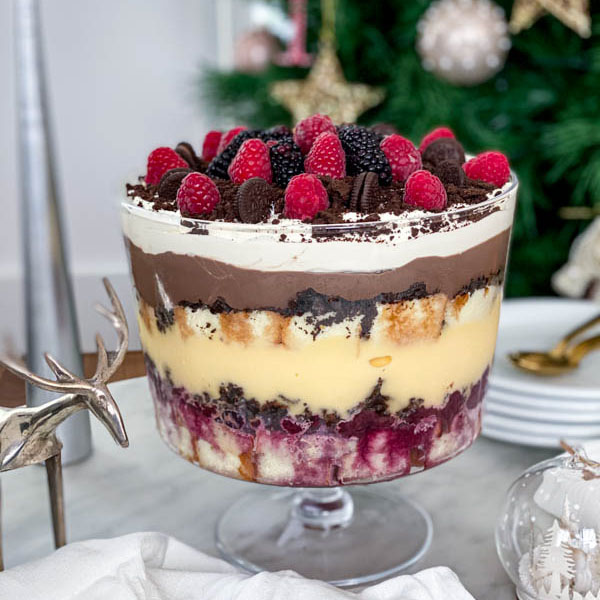 The finished trifle is on the table with plates and spoons in the background.