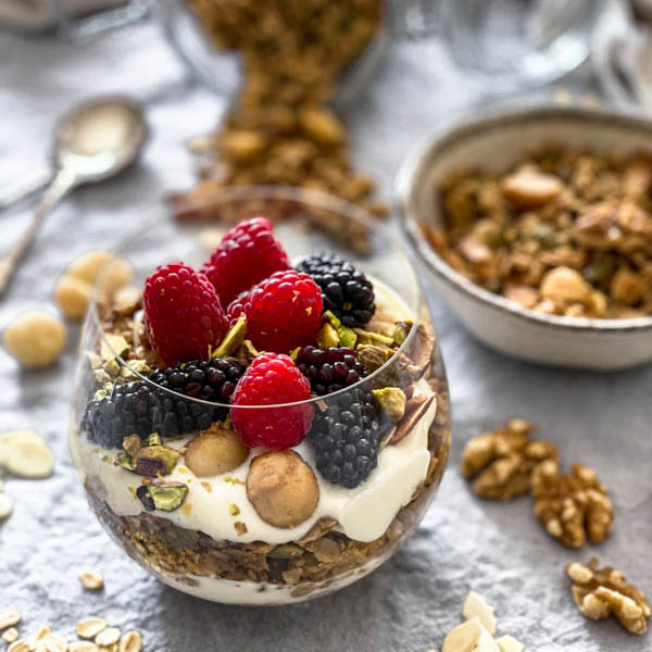 A close up of the parfait glass with granola, yoghurt and fresh berries.