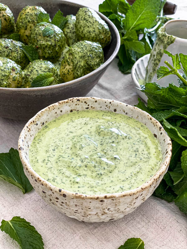 The Mint Dressing is in a bowl with mint leaves scattered around it and a bowl of the Potato Salad in the background.