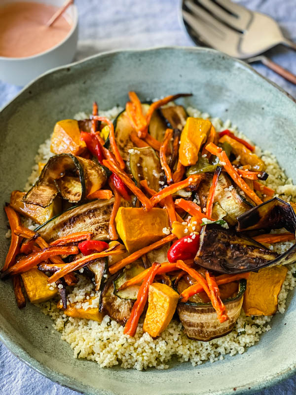 The bowl of Grilled Vegetable and Couscous Salad is in a bowl on a table with the Red Pepper Mayo and salad servers in the background.