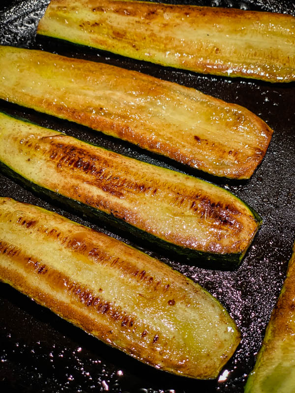 Charred and browned zucchini slices are cooking on a bbq plate.