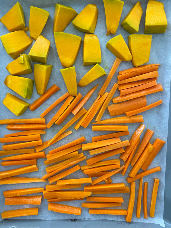 Carrot sticks and pumpkin pieces are evenly spread out on an oven tray lined with baking paper, ready for cooking in the oven.