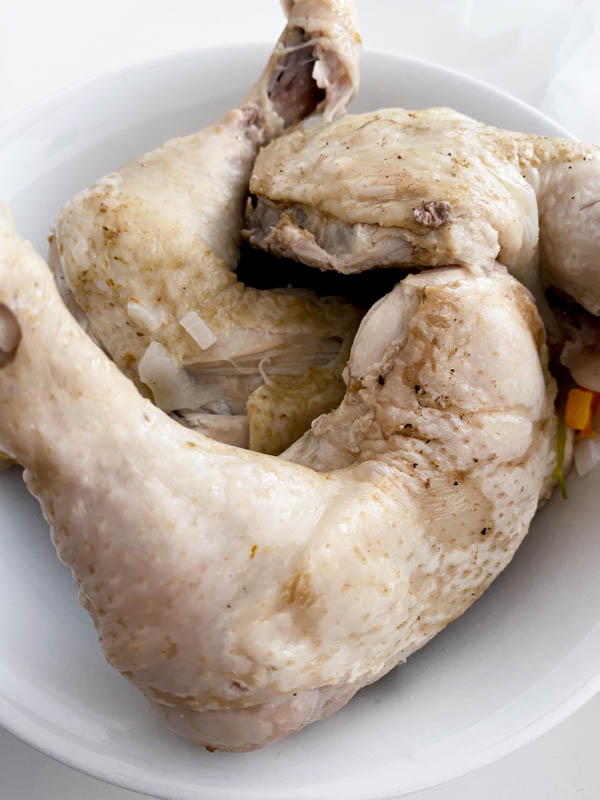 The chicken pieces have been cooked and are now resting in a bowl to cool down, before the meat is removed from the bones and added back into the soup.