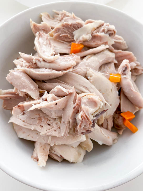 The cooked chicken meat has been removed from the bones and about to be added back into the soup.