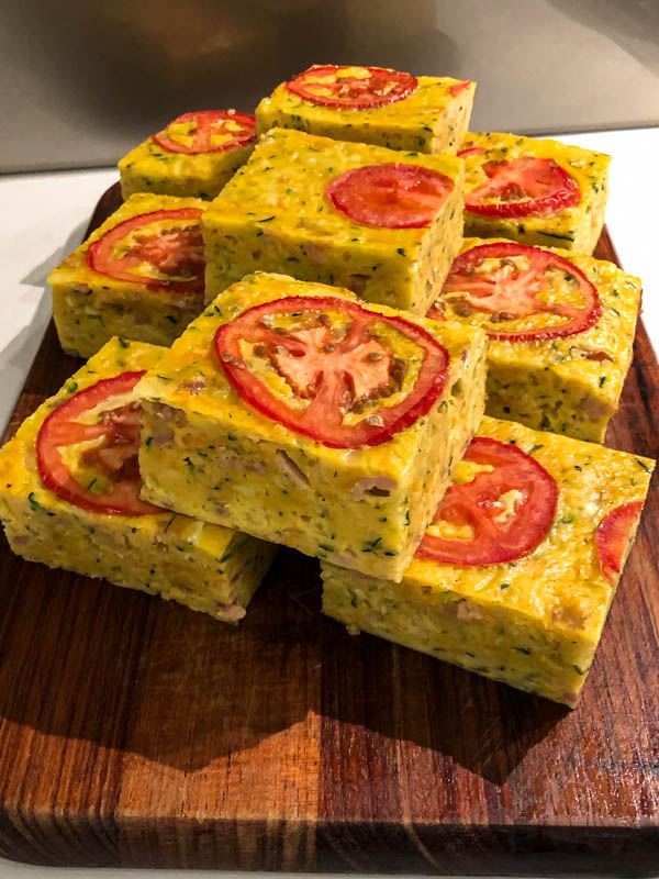 Squares of Zucchini Slice on a wooden board.