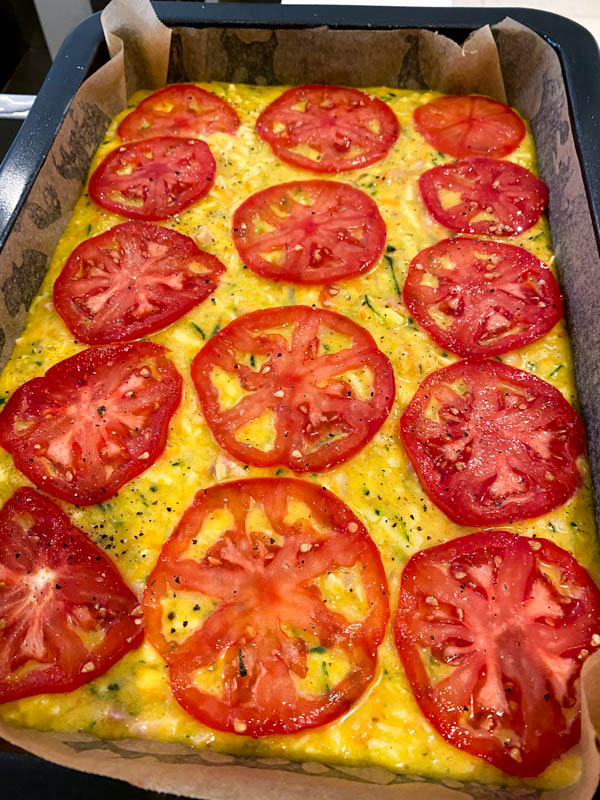 The zucchini slice batter is now in a rectangle baking pan and is topped with sliced tomatoes, ready to be cooked in the oven.