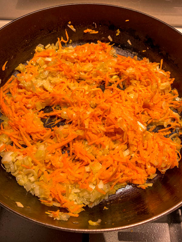 The chopped onions and grated carrot are being sautéed in a frying pan.