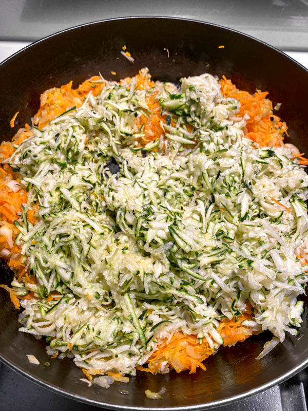The grated zucchini is now added to the frying pan.