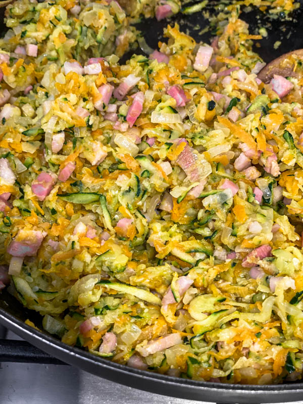A close up showing the sautéed onions, carrot, zucchini, garlic and bacon that is now ready for the eggs and flour to be added.