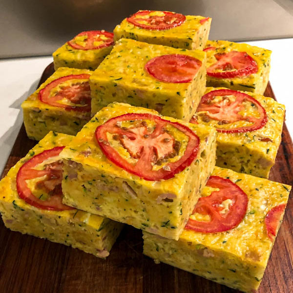 A close up of the portioned squares of zucchini slice presented on a wooden chopping board.