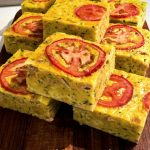 The zucchini slice is cut into squares and sitting on a wooden chopping board.