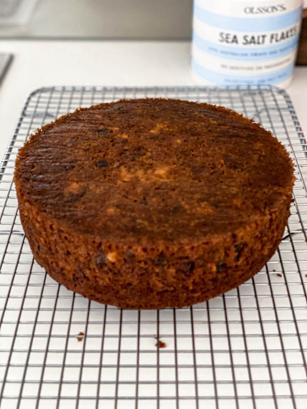 The cake is now cooked and resting upside down on a wire cake rack.