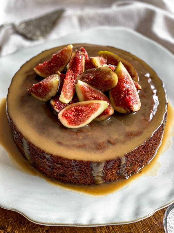 The Sticky Date Pudding is on a plate with the caramel sauce poured over the top. It is decorated with a pile of fresh quartered figs on top.