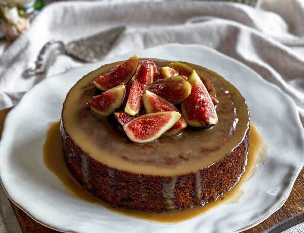 The Sticky Date Pudding is on a plate on top of a wooden board and sitting on a linen tablecloth.