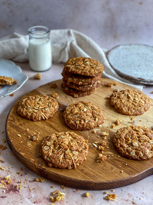 There are a pile of 4 biscuits and some single ones on a round wooden tray with biscuit crumbs around them.