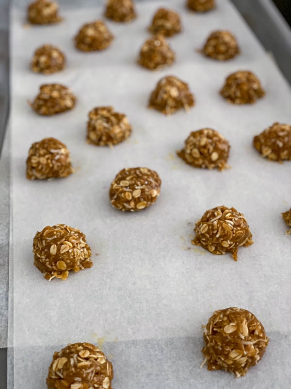 The balls of biscuit dough are on an oven tray lined with baking paper, ready for the oven.