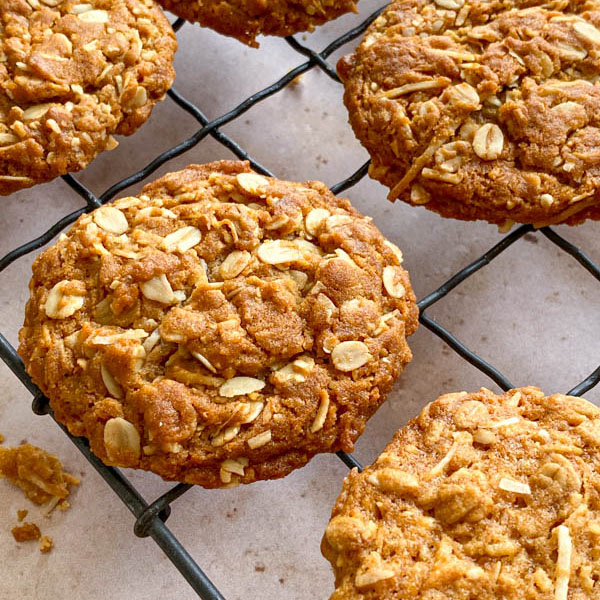 A side on view of one of the Chewy Anzac Biscuits resting on the wire cooling rack.